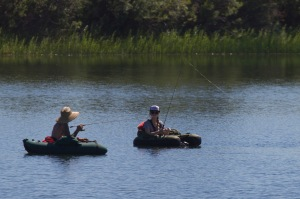 Two young women fishing from belly boats on Sunset lake, near Hygiene, CO