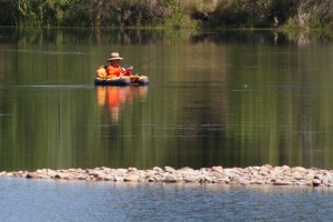 A friendly man fishing from a belly boat on Heron Lake, near Hygiene, CO