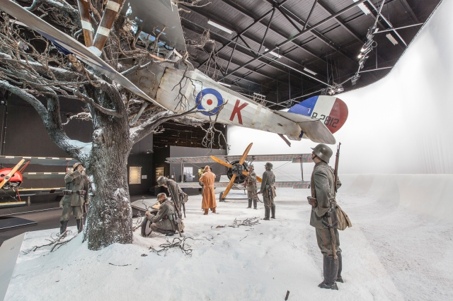 Germans guard a Nieuport 27 crashed in a tree while a Siemens Schukert sits in the snow.