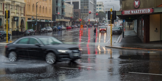 Wellington in the rain with passing car raising spray