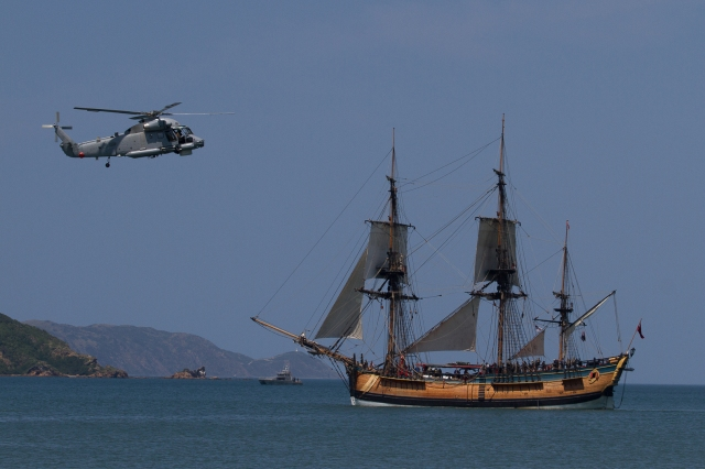 An RNZN sea sprite helicopter hovering over the Endeavour replica